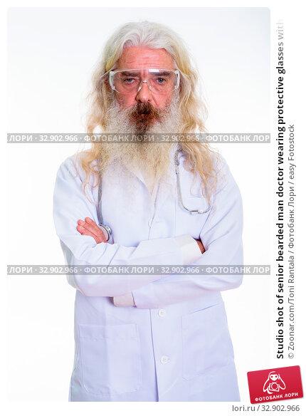 Studio shot of senior bearded man doctor wearing protective glasses with arms crossed. Стоковое фото, фотограф Zoonar.com/Toni Rantala / easy Fotostock / Фотобанк Лори