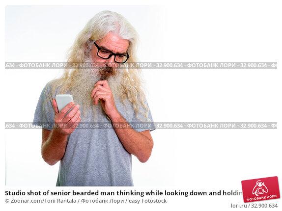 Studio shot of senior bearded man thinking while looking down and holding mobile phone. Стоковое фото, фотограф Zoonar.com/Toni Rantala / easy Fotostock / Фотобанк Лори