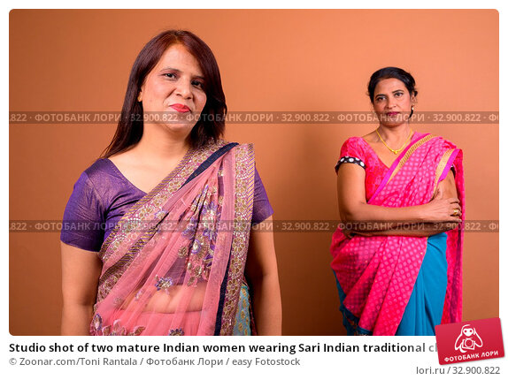 Studio shot of two mature Indian women wearing Sari Indian traditional clothes together against brown background. Стоковое фото, фотограф Zoonar.com/Toni Rantala / easy Fotostock / Фотобанк Лори