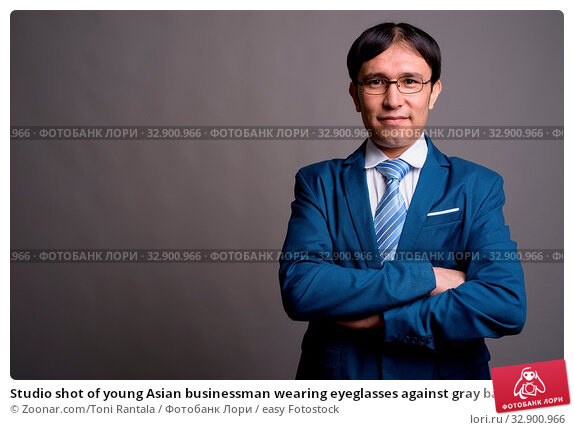 Studio shot of young Asian businessman wearing eyeglasses against gray background. Стоковое фото, фотограф Zoonar.com/Toni Rantala / easy Fotostock / Фотобанк Лори