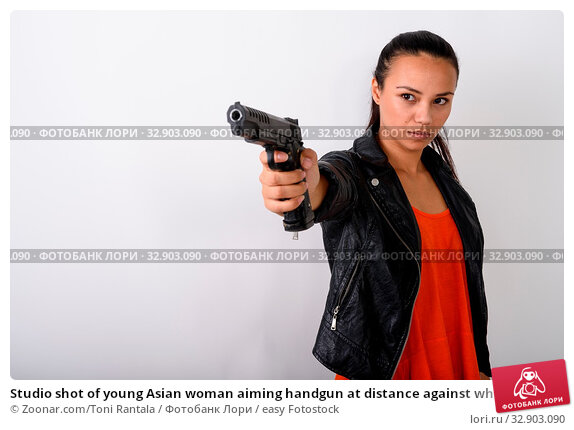 Studio shot of young Asian woman aiming handgun at distance against white background. Стоковое фото, фотограф Zoonar.com/Toni Rantala / easy Fotostock / Фотобанк Лори