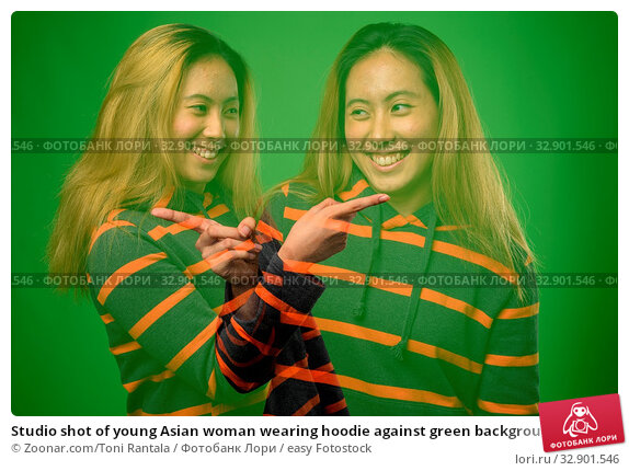 Studio shot of young Asian woman wearing hoodie against green background. Стоковое фото, фотограф Zoonar.com/Toni Rantala / easy Fotostock / Фотобанк Лори