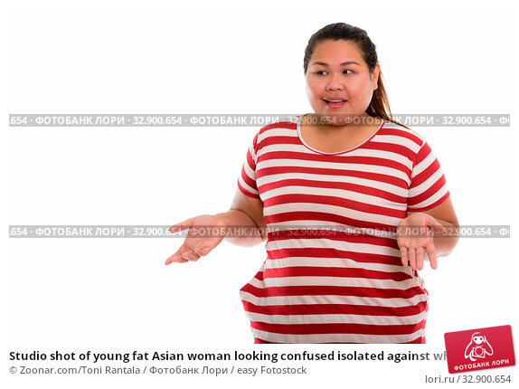 Studio shot of young fat Asian woman looking confused isolated against white background. Стоковое фото, фотограф Zoonar.com/Toni Rantala / easy Fotostock / Фотобанк Лори