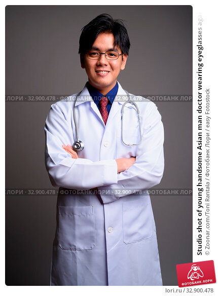 Studio shot of young handsome Asian man doctor wearing eyeglasses against gray background. Стоковое фото, фотограф Zoonar.com/Toni Rantala / easy Fotostock / Фотобанк Лори