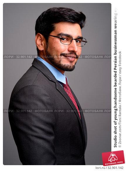 Studio shot of young handsome bearded Persian businessman wearing eyeglasses against gray background. Стоковое фото, фотограф Zoonar.com/Toni Rantala / easy Fotostock / Фотобанк Лори