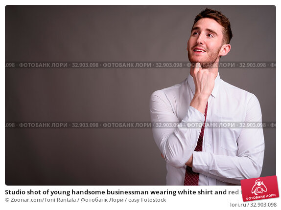 Studio shot of young handsome businessman wearing white shirt and red tie against gray background. Стоковое фото, фотограф Zoonar.com/Toni Rantala / easy Fotostock / Фотобанк Лори