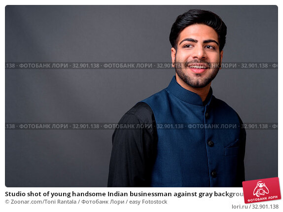 Studio shot of young handsome Indian businessman against gray background. Стоковое фото, фотограф Zoonar.com/Toni Rantala / easy Fotostock / Фотобанк Лори