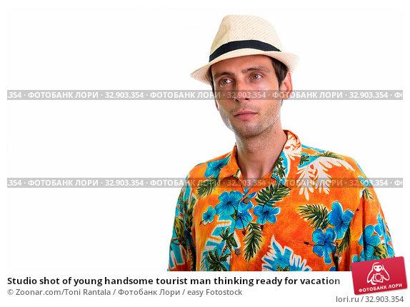 Studio shot of young handsome tourist man thinking ready for vacation. Стоковое фото, фотограф Zoonar.com/Toni Rantala / easy Fotostock / Фотобанк Лори