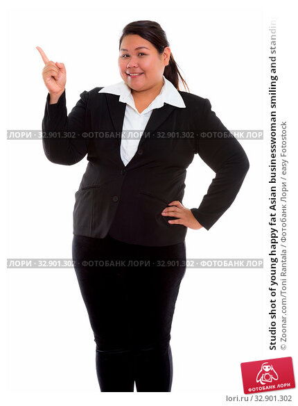 Studio shot of young happy fat Asian businesswoman smiling and standing while pointing finger up. Стоковое фото, фотограф Zoonar.com/Toni Rantala / easy Fotostock / Фотобанк Лори