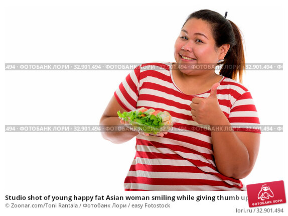Studio shot of young happy fat Asian woman smiling while giving thumb up and holding fresh vegetable wrap. Стоковое фото, фотограф Zoonar.com/Toni Rantala / easy Fotostock / Фотобанк Лори