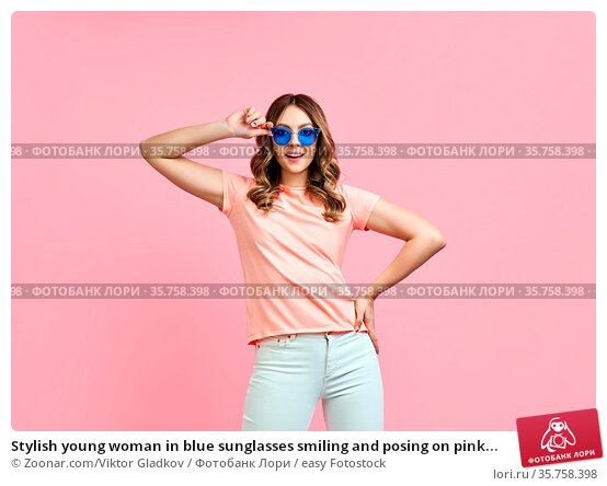 Stylish young woman in blue sunglasses smiling and posing on pink... Стоковое фото, фотограф Zoonar.com/Viktor Gladkov / easy Fotostock / Фотобанк Лори