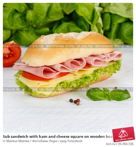 Sub sandwich with ham and cheese square on wooden board wood. Стоковое фото, фотограф Markus Mainka / easy Fotostock / Фотобанк Лори