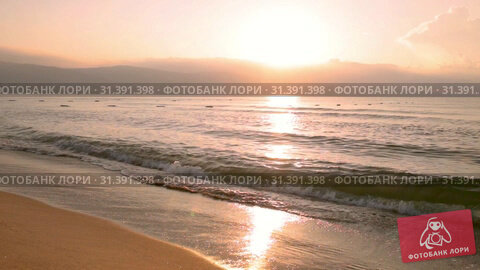 Sunrise over the sea, the waves of the surf rolled on the sandy beach. Стоковое видео, видеограф Юлия Бабкина / Фотобанк Лори