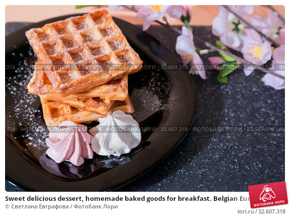 Sweet delicious dessert, homemade baked goods for breakfast. Belgian European soft waffles on a black plate and meringue. Стоковое фото, фотограф Светлана Евграфова / Фотобанк Лори