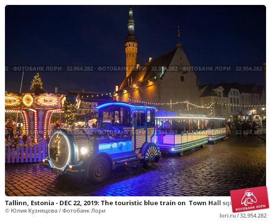 Tallinn, Estonia - DEC 22, 2019: The touristic blue train on  Town Hall square in night time. Редакционное фото, фотограф Юлия Кузнецова / Фотобанк Лори