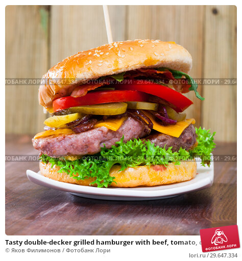 Купить «Tasty double-decker grilled hamburger with beef, tomato, cheese, cucumber», фото № 29647334, снято 24 апреля 2019 г. (c) Яков Филимонов / Фотобанк Лори