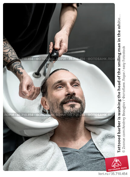Tattooed barber is washing the head of the smiling man in the white... Стоковое фото, фотограф Zoonar.com/Andrey Bezuglov / easy Fotostock / Фотобанк Лори