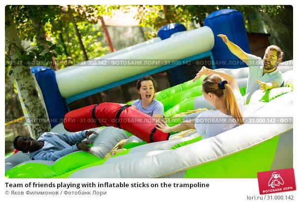 Купить «Team of friends playing with inflatable sticks on the trampoline», фото № 31000142, снято 21 августа 2019 г. (c) Яков Филимонов / Фотобанк Лори