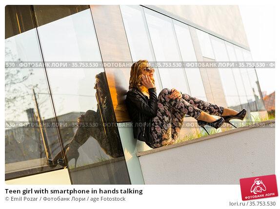 Teen girl with smartphone in hands talking. Стоковое фото, фотограф Emil Pozar / age Fotostock / Фотобанк Лори