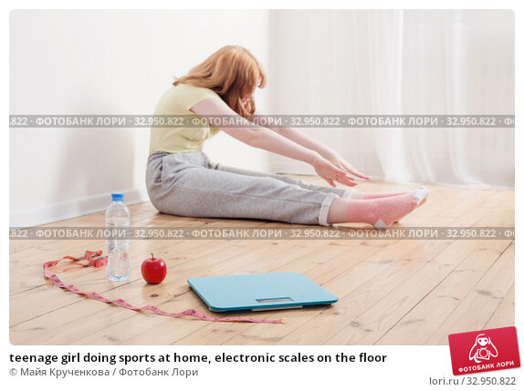 teenage girl doing sports at home, electronic scales on the floor. Стоковое фото, фотограф Майя Крученкова / Фотобанк Лори