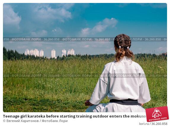 Teenage girl karateka before starting training outdoor enters the mokuso meditative state in the seiza pose. Стоковое фото, фотограф Евгений Харитонов / Фотобанк Лори