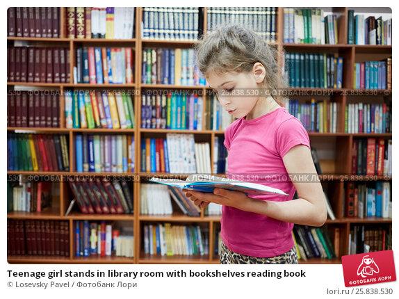 Купить «Teenage girl stands in library room with bookshelves reading book», фото № 25838530, снято 26 июня 2015 г. (c) Losevsky Pavel / Фотобанк Лори