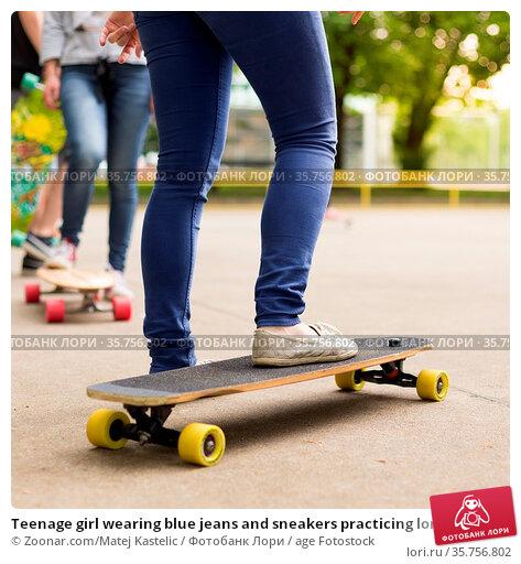 Teenage girl wearing blue jeans and sneakers practicing long board... Стоковое фото, фотограф Zoonar.com/Matej Kastelic / age Fotostock / Фотобанк Лори
