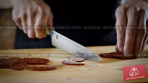 The chef cutting in half pieces of spicy dry sausage in the kitchen. 4K, видеоролик № 26930342, снято 31 июля 2017 г. (c) ActionStore / Фотобанк Лори