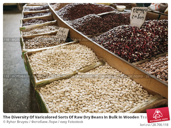 Купить «The Diversity Of Varicolored Sorts Of Raw Dry Beans In Bulk In Wooden Trays For Sale At Showcase Of Market, Bazar.», фото № 28700118, снято 28 мая 2016 г. (c) easy Fotostock / Фотобанк Лори