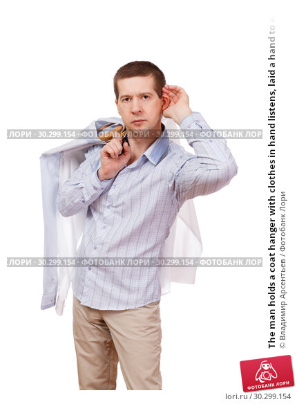 Купить «The man holds a coat hanger with clothes in hand listens, laid a hand to an ear, on a white background», фото № 30299154, снято 7 марта 2019 г. (c) Владимир Арсентьев / Фотобанк Лори