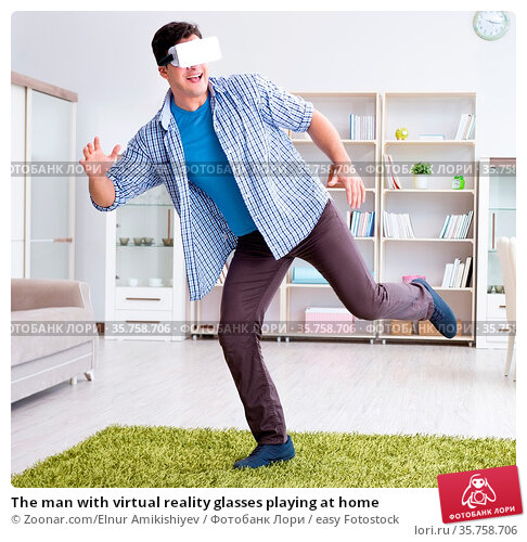 The man with virtual reality glasses playing at home. Стоковое фото, фотограф Zoonar.com/Elnur Amikishiyev / easy Fotostock / Фотобанк Лори