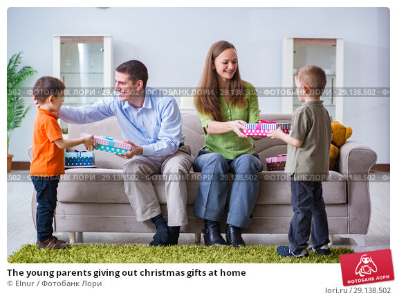 Купить «The young parents giving out christmas gifts at home», фото № 29138502, снято 21 января 2017 г. (c) Elnur / Фотобанк Лори