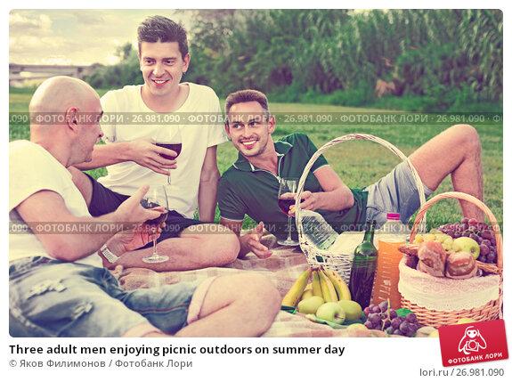 Купить «Three adult men enjoying picnic outdoors on summer day», фото № 26981090, снято 23 августа 2017 г. (c) Яков Филимонов / Фотобанк Лори