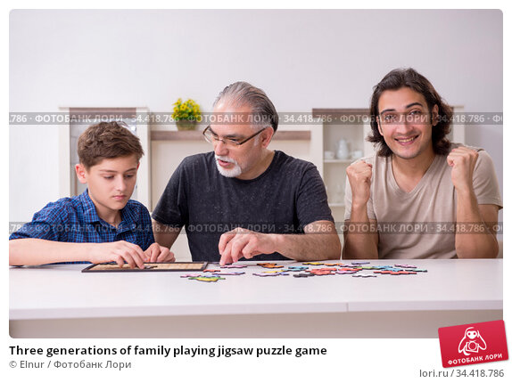 Three generations of family playing jigsaw puzzle game. Стоковое фото, фотограф Elnur / Фотобанк Лори