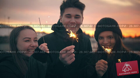 Купить «Three happy friends having fun together with sparkler at sunset outdoors», видеоролик № 28307682, снято 12 декабря 2018 г. (c) Константин Шишкин / Фотобанк Лори