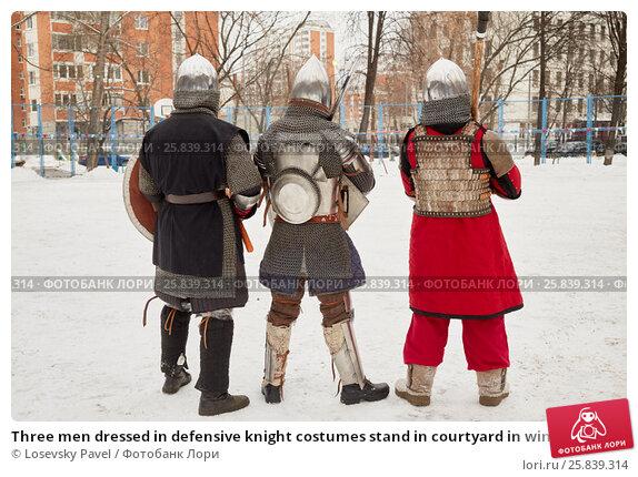 Купить «Three men dressed in defensive knight costumes stand in courtyard in winter», фото № 25839314, снято 28 декабря 2014 г. (c) Losevsky Pavel / Фотобанк Лори