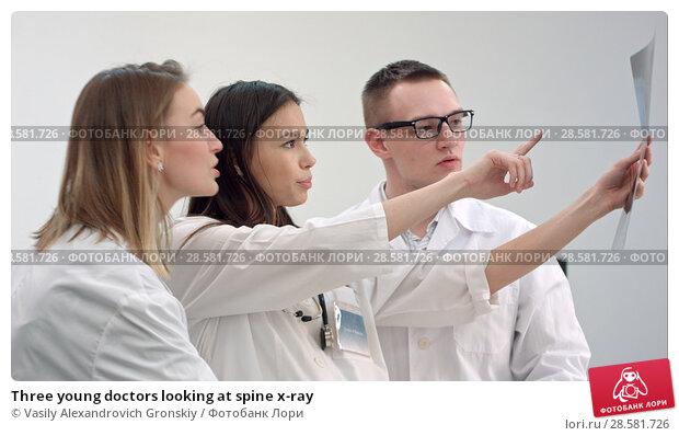 Купить «Three young doctors looking at spine x-ray», фото № 28581726, снято 21 июня 2018 г. (c) Vasily Alexandrovich Gronskiy / Фотобанк Лори