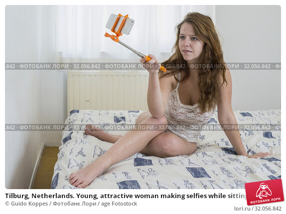 Tilburg, Netherlands. Young, attractive woman making selfies while sitting on her bed. Стоковое фото, фотограф Guido Koppes / age Fotostock / Фотобанк Лори