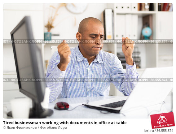 Tired businessman working with documents in office at table. Стоковое фото, фотограф Яков Филимонов / Фотобанк Лори