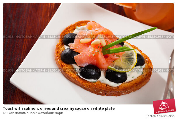 Toast with salmon, olives and creamy sauce on white plate. Стоковое фото, фотограф Яков Филимонов / Фотобанк Лори