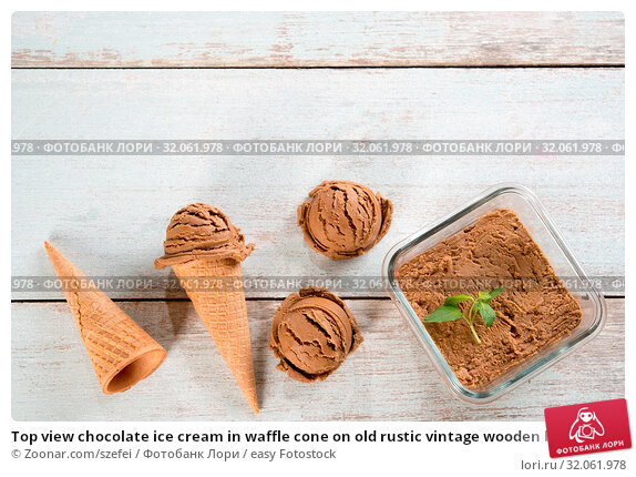 Top view chocolate ice cream in waffle cone on old rustic vintage wooden background. Copy space on above. Стоковое фото, фотограф Zoonar.com/szefei / easy Fotostock / Фотобанк Лори