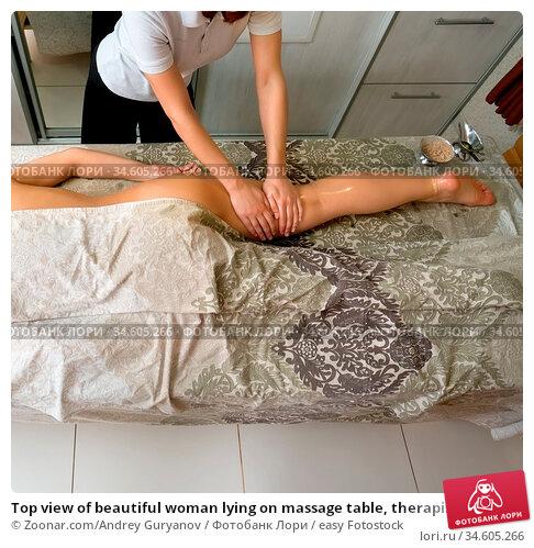 Top view of beautiful woman lying on massage table, therapist massaging... Стоковое фото, фотограф Zoonar.com/Andrey Guryanov / easy Fotostock / Фотобанк Лори