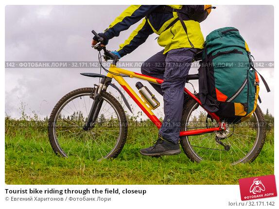 Купить «Tourist bike riding through the field, closeup», фото № 32171142, снято 3 сентября 2019 г. (c) Евгений Харитонов / Фотобанк Лори