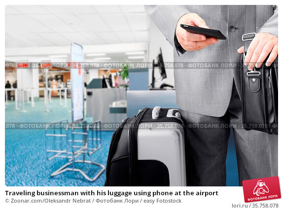 Traveling businessman with his luggage using phone at the airport. Стоковое фото, фотограф Zoonar.com/Oleksandr Nebrat / easy Fotostock / Фотобанк Лори