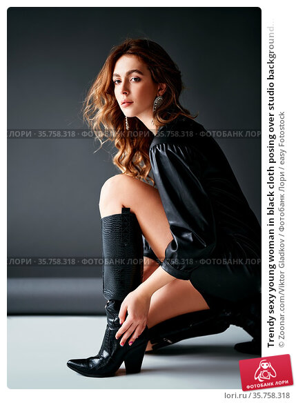 Trendy sexy young woman in black cloth posing over studio background... Стоковое фото, фотограф Zoonar.com/Viktor Gladkov / easy Fotostock / Фотобанк Лори