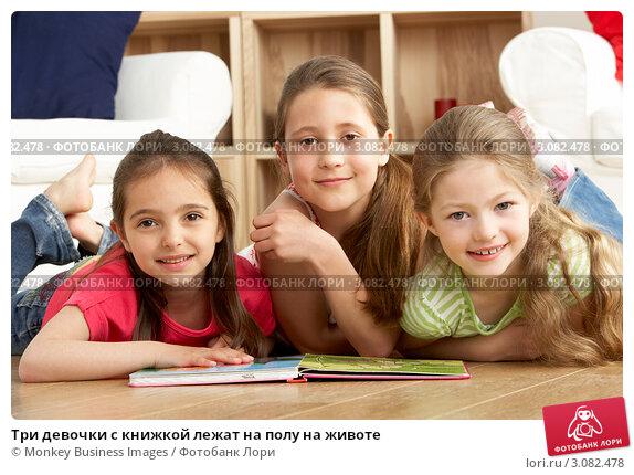 Купить «Три девочки с книжкой лежат на полу на животе», фото № 3082478, снято 14 апреля 2009 г. (c) Monkey Business Images / Фотобанк Лори