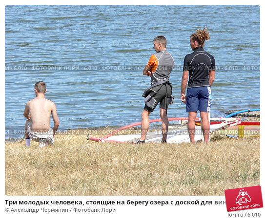 Три молодых человека, стоящие на берегу озера с доской для виндсерфинга , фото № 6010, снято 15 августа 2005 г. (c) Александр Чермянин / Фотобанк Лори