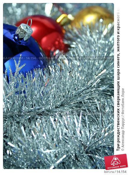 Три рождественских сверкающих шара синего, желтого и красного цвета на фоне серебристой новогодней мишуры, фото № 14154, снято 24 ноября 2006 г. (c) Александр Паррус / Фотобанк Лори