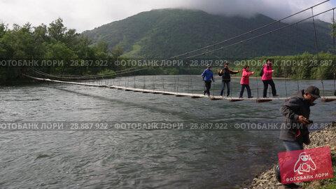 Купить «Туристы переходят горную речку по подвесному мосту», видеоролик № 28887922, снято 4 августа 2018 г. (c) А. А. Пирагис / Фотобанк Лори