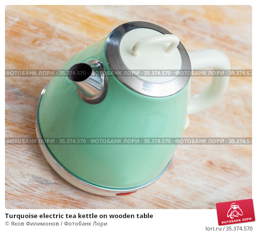 Turquoise electric tea kettle on wooden table. Стоковое фото, фотограф Яков Филимонов / Фотобанк Лори